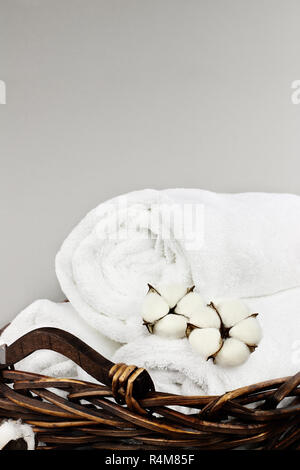 Laundry basket filled white fluffy towels, cotton flowers and a bottle of liquid soap against a grey background with free space for text. - Stock Image