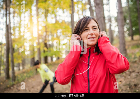 Two active female runners stretching outdoors in forest in autumn nature after the run. - Stock Image