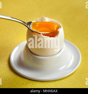 Soft-boiled egg in a porcelain egg cup with a little spoon on yellow background. - Stock Image