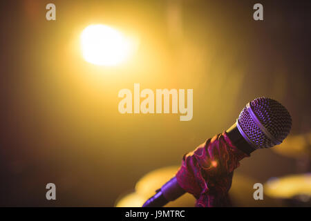 Microphone in illuminated nightclub - Stock Image