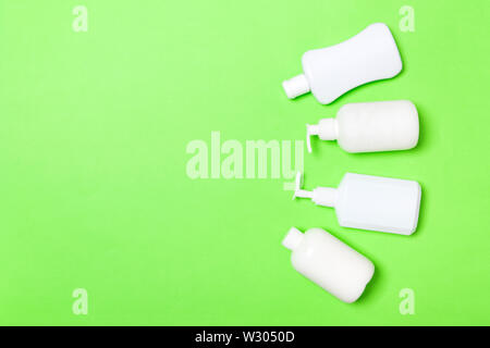 Set of White Cosmetic containers isolated on green background, top view with copy space. Group of plastic bodycare bottle containers with empty space - Stock Image