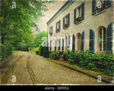 View of Maison du Jardinage with pretty blue shutters at Parc de Bercy in Paris, France. Brick pavement, trees and - Stock Image