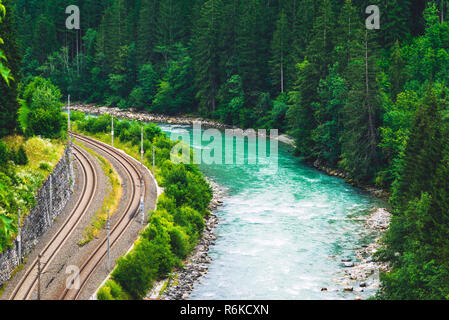 Beautiful railway through the forest near mountain road - Stock Image
