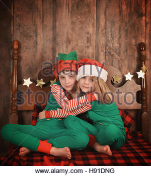 Little children wearing pajamas with Christmas hats hugging each other on a bed for a family at home concept or - Stock Image
