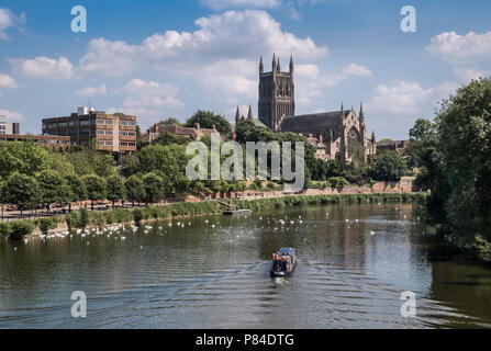 A barge sailing on the River Severn through the City of Worcester, with Worcester Cathedral in the backgound, Worcestershire, West Midlands, England. - Stock Image