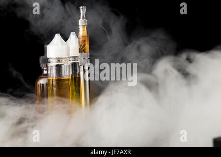 Electronic cigarette with bottles and big cloud of smoke - Stock Image