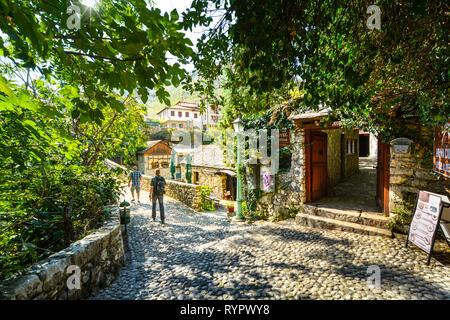 Tourists walk a cobblestone path over a bridge in the medieval city of Mostar, Bosnia on an autumn morning. - Stock Image
