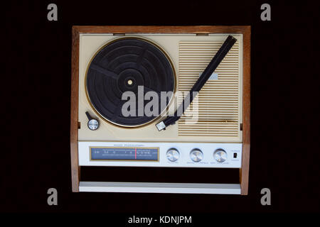 Old radio-phonograph. Turntable platter, tonearm, AM radio dial, buttons, and switches. The radio-gramophone is - Stock Image
