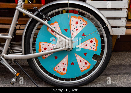 Rear wheel of a bicycle decorated as pizza - Stock Image