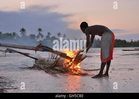 geography / travel, Tanzania, Zanzibar, fisherman fumes with palm leaf his boat, to E flat in front of wood worm - Stock Image