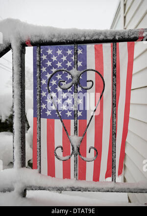 Merrick, New York, U.S. February 13, 2014 - As yet another snow storm slams into Long Island, a snowy American Flag decorates the front stoop railing of a home. New York's governor declared a state of emergency, and 5 to 14 inches of snow are expected to fall on Nassau and Suffolk Counties through to the evening, Credit:  Ann E Parry/Alamy Live News - Stock Image
