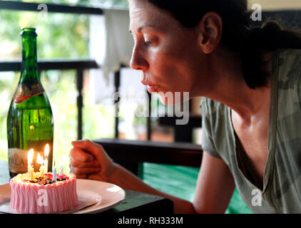Woman blow out candels on birthday cake - Stock Image