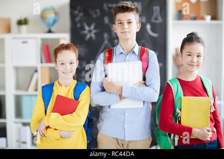 Group of two pretty schoolgirls and clever schoolboy with books standing in front of camera in classroom - Stock Image
