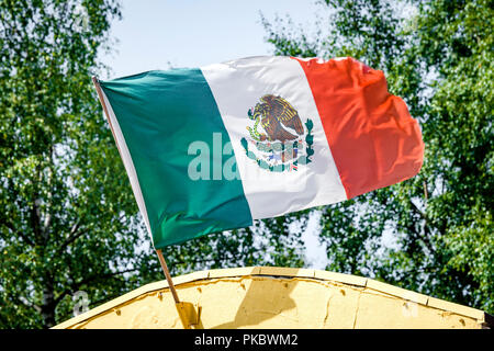 Mexican flag on a yellow building waving in the wind in Mexico - Stock Image