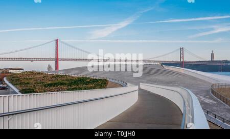 Pedestrian bridge leading to Landmark 25 of April bridge on Tagus River, Lisbon, Portugal. - Stock Image
