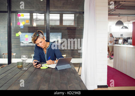 Woman texting by table - Stock Image