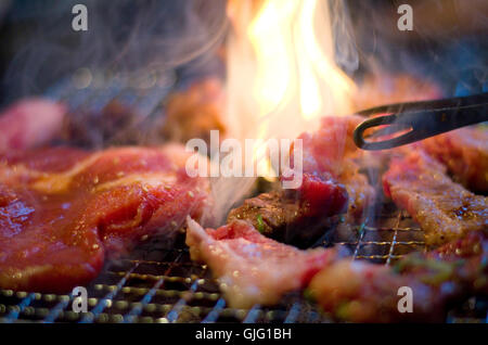Thin slices of pork and beef on a Korean style barbecue. - Stock Image