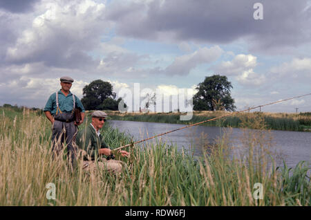 1960s, two anglers on the river Great Ouse, Norfolk, England, UK, fishing from the rushes on the riverbank. At 143 miles in length, it is the longest of several British rivers called 'Ouse' and one of the longest in the UK. - Stock Image
