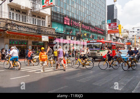 Bangkok, Thailand - 7th March 2017: Tourists on a bicycle tour crossing Yaowarat Road. This is the main road through Chinatown. - Stock Image