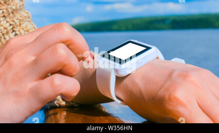Woman using wearable smart watch with white empty display - Stock Image