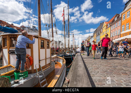 A man painting his boat along Nyhavn Canal, Copenhagen, Denmark - Stock Image