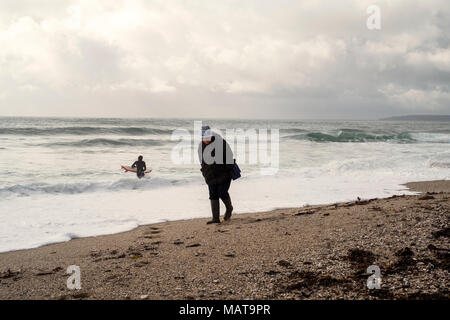 Gyllyngvase beach, Falmouth. 4th Apr, 2018. UK Weather: Surfer braves cold water  at Gyllyngvase beach, Falmouth. A woman walks along Falmouth's Gyllyngvase beach as a surfer enters the water Credit: Mick Buston/Alamy Live News - Stock Image