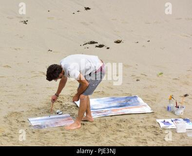 A man painting on a sandy beach, Sennen Cove,Cornwall,England,UK - Stock Image