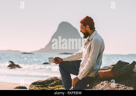 Man relaxing at ocean beach holding tea cup solo traveling lifestyle adventure summer vacations in Norway breakfast outdoor - Stock Image