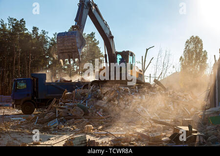 The excavator loads the remains of the destroyed building in the car - Stock Image