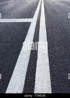 Asphalt road with white marking diminishing perspective - Stock Image