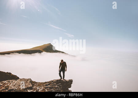 Tourist man exploring mountains over clouds active adventure solo traveling lifestyle summer vacations outdoor - Stock Image
