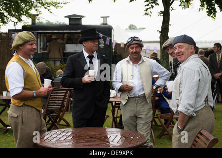 Chichester, West Sussex, UK. 13th Sep, 2013. Goodwood Revival. Goodwood Racing Circuit, West Sussex - Friday 13th September. Five gentlemen in period clothing relax with a hot drink at one of the cafe areas. © MeonStock/Alamy Live News - Stock Image