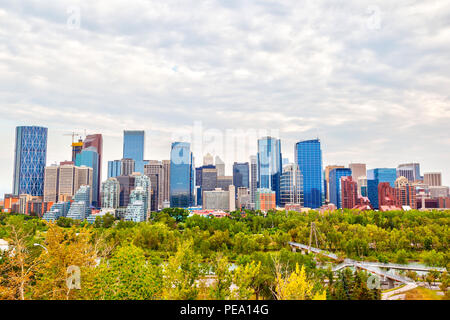 Calgary's downtown skyline showing corporate offices and the financial district with public park and Bow River in the foreground. - Stock Image