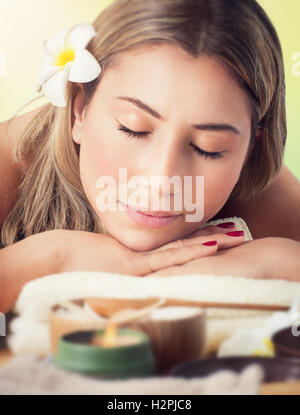 Closeup portrait of a peaceful woman with closed eyes lying down on a massage table in the spa salon, healthy lifestyle - Stock Image