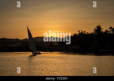 Silhouette of a felucca sailing on Nile River at sunset, Aswan, Egypt - Stock Image