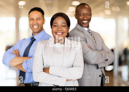 multiracial vehicle sales team with arms crossed inside car showroom - Stock Image