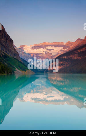 Glacial Lake Louise with Victoria glacier and mountains reflected in emerald water, Banff National Park, Alberta, - Stock Image