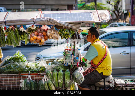 BANGKOK, THAILAND - NOVEMBER 2018: Salesman is riding on his bike with vegetables and fruits in Bangkok, Thailand - Stock Image