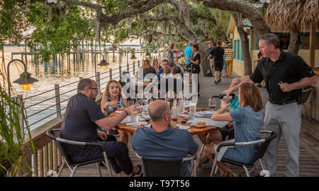 Sunset dining under Florida live oaks on the waterfront deck at Caps on the Water, a local seafood restaurant on the Intracoastal in St. Augustine, FL. - Stock Image