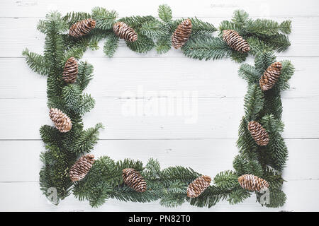 Christmas tree branches on wood background - Stock Image