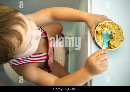 2 years baby boy eating nougat ice cream cup. Overhead view - Stock Image