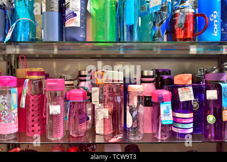Display of refillable environmentally friendly drinking water bottles on shelves for sale in shop - Stock Image