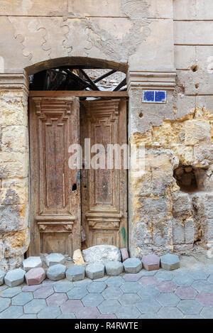 Broken wooden door on grunge stone bricks wall in abandoned Darb El Labana district, Cairo, Egypt - Stock Image