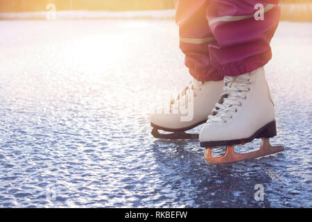 Close up view of young 4 year old girl wearing white figure skates, skating on frozen lake in nature outdoors on cold sunny winter day. Hobby concept. - Stock Image