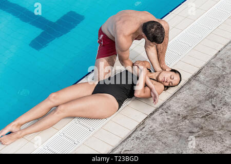 Lifeguard rescue procedure - positioning woman. - Stock Image