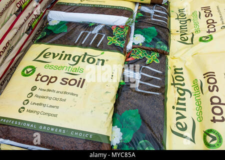 A stack of bags of Levington Top Soil in a garden centre - Stock Image