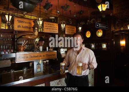 Frankfurt german waiter with two beers at iconic historic beer bar kneipe City Hall Rathausplatz - Stock Image