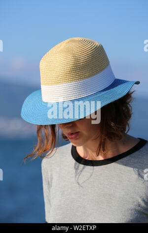 Mysterious Young Woman In Straw Hat At The Beach. Close Up Portrait - Stock Image