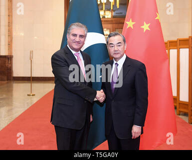 Beijing, China. 24th Apr, 2019. Chinese State Councilor and Foreign Minister Wang Yi (R) meets with Pakistani Foreign Minister Shah Mahmood Qureshi in Beijing, capital of China, April 24, 2019. Credit: Shen Hong/Xinhua/Alamy Live News - Stock Image
