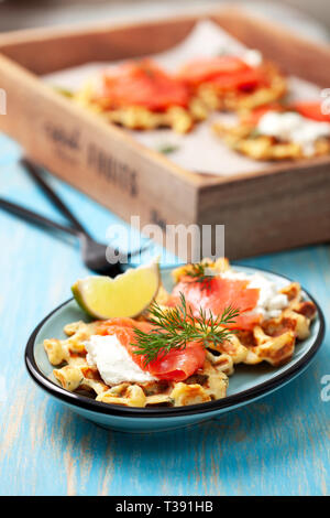 potato waffles with salmon, cream cheese on a blue wooden background. - Stock Image
